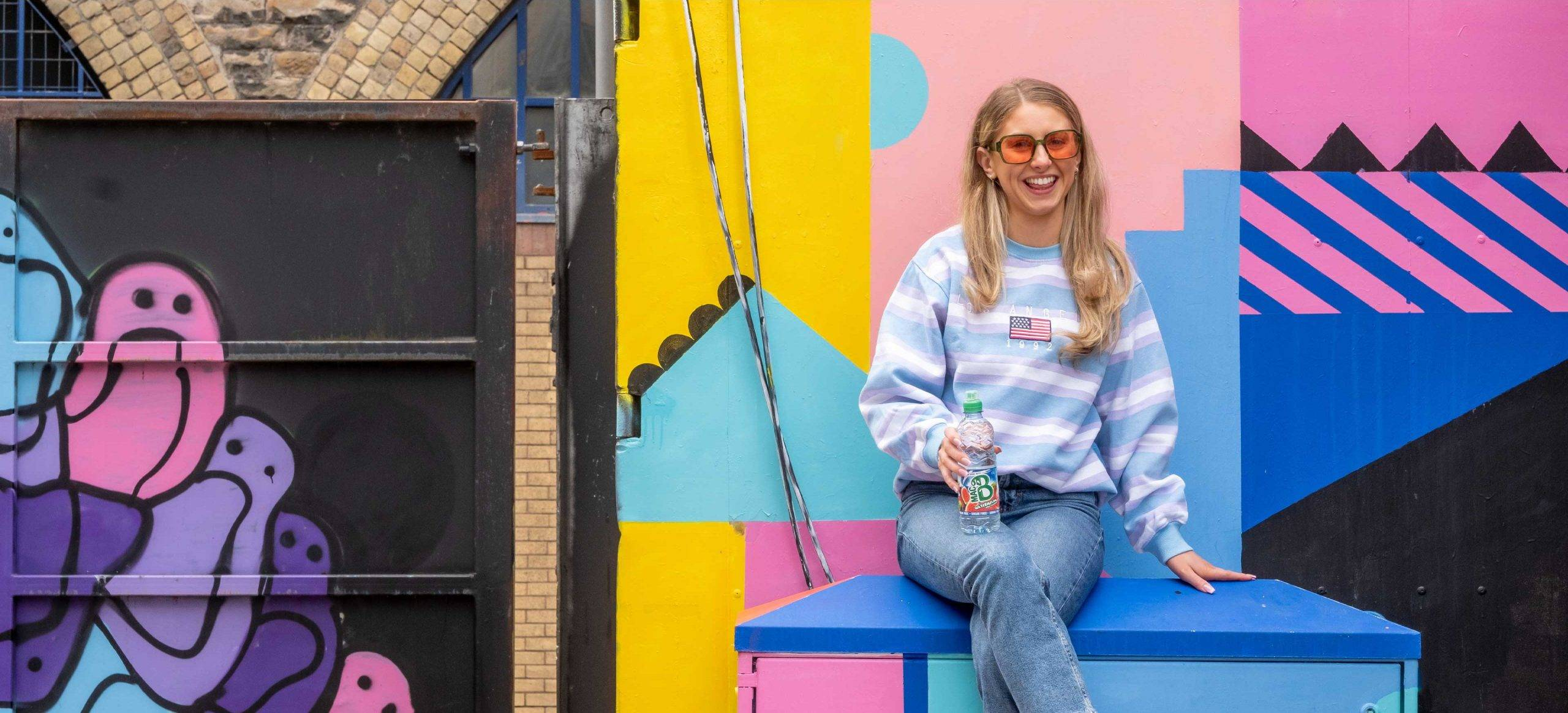A young woman in front of a wall mural wearing sunglasses, laughing and drinking a bottle of Macb Flavoured Spring Water