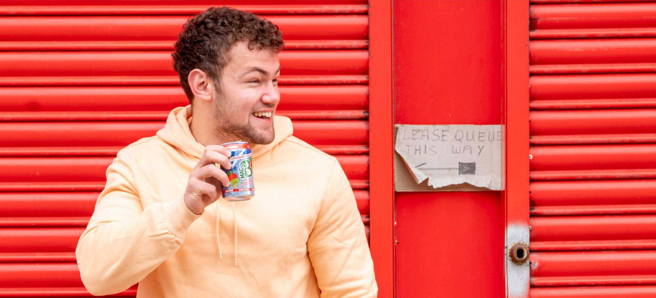 A young man drinking a can of Macb sparkling spring water in front of a red shop frontage