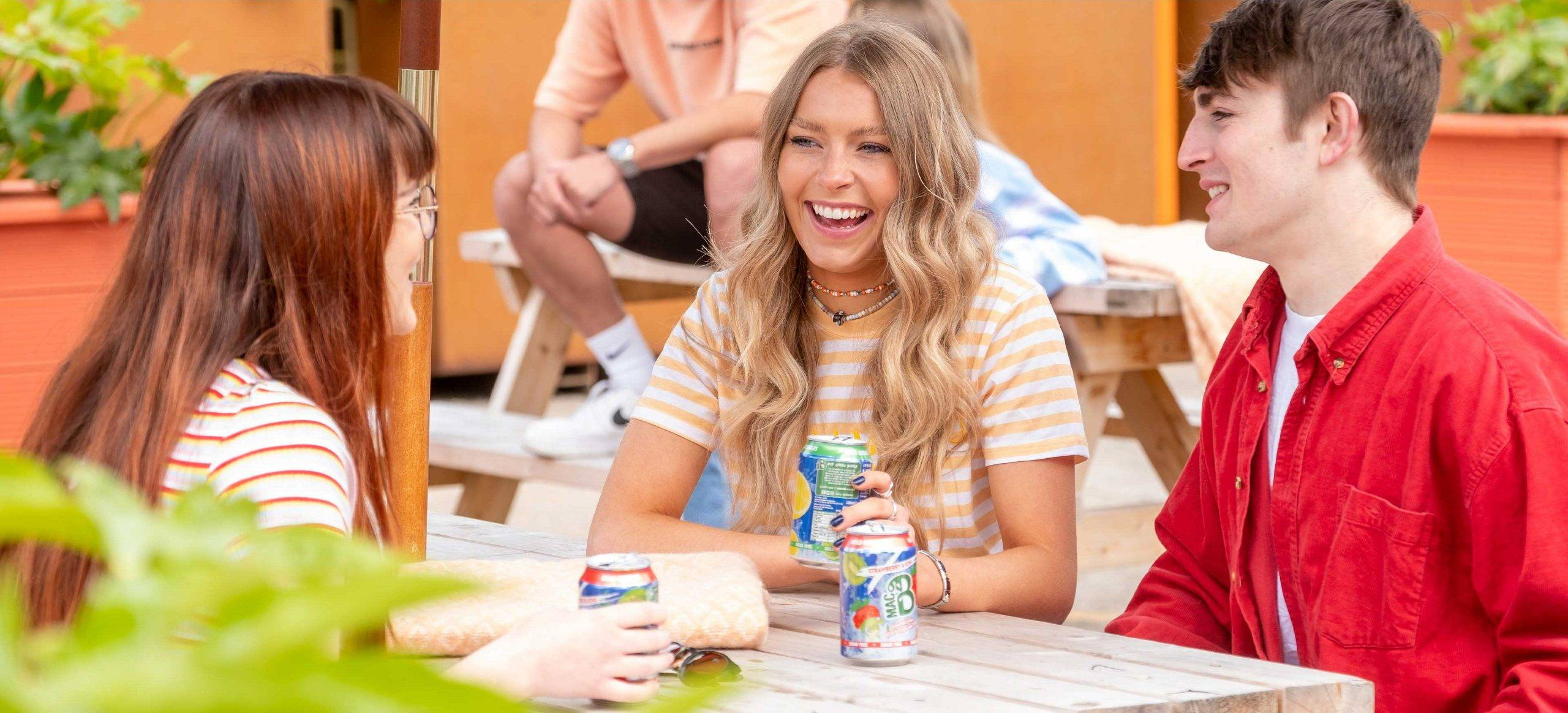 A group of young people laughing at a table, drinking cans of Macb sparkling flavoured spring water