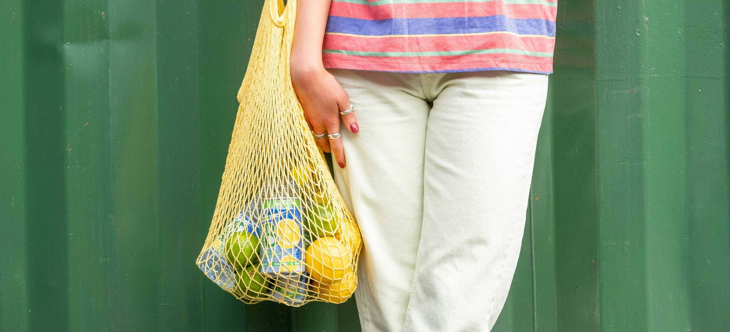 A woman holding a bag of lemons and limes, with a can of Macb sparkling lemon and lime flavoured spring water