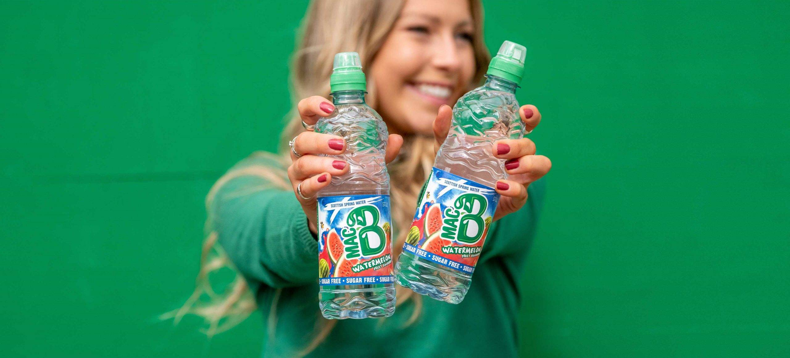A woman holding two bottles of Macb Watermelon flavoured spring water