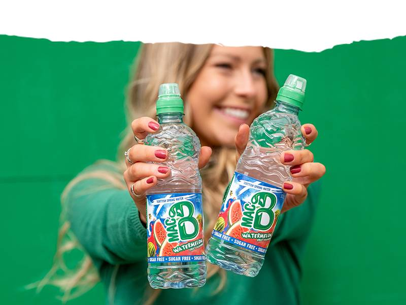 A woman with a green jumper holding two bottles of Macb watermelon flavoured spring water