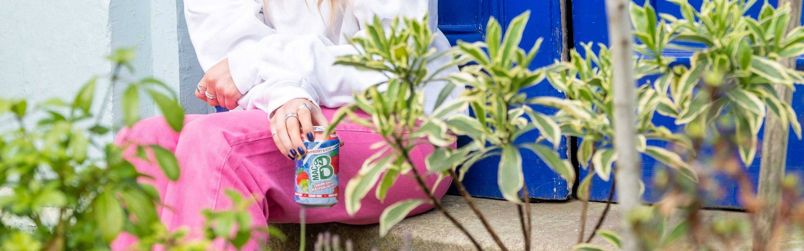 A woman sitting down by some flowers in purple trousers, drinking from a can of Macb flavoured sparkling spring water